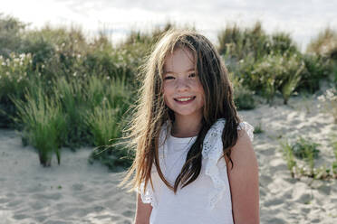 Smiling girl standing on sand at beach during sunny day - OGF00614