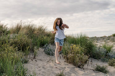 Cheerful girl running on sand at beach against cloudy sky - OGF00617