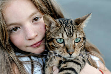 Cute girl carrying cat on sunny day - OGF00623
