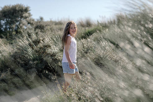Girl standing in between of bush on sunny day - OGF00626