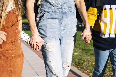 Midsection of mother, daughter and son holding hands walking in public park on sunny day - JCMF01550