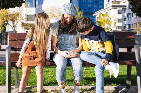 Mother with kids using smart phone sitting on bench in public park during sunny day - JCMF01553