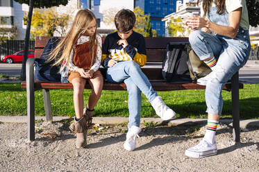 Low section of mother with kids using smart phone while sitting on bench in public park during sunny day - JCMF01556