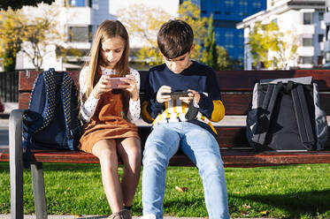Brother and sister using smart phone while sitting on bench in public park during sunny day - JCMF01559
