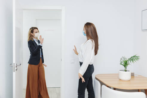 Woman wearing face mask waving hand at door in office - MRRF00627