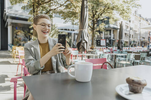 Woman taking selfie on smart phone while sitting in outdoor cafe - MFF06707