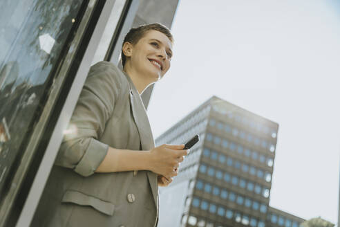 Smiling woman using smart phone while standing on street in city - MFF06722