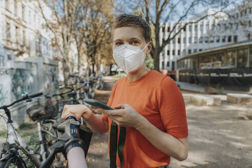 Smiling woman wearing protective face mask using smart phone while standing on electric push scooter - MFF06737