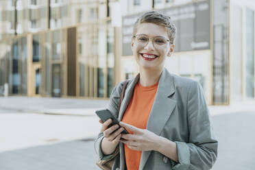 Mid adult woman smiling while holding smart phone standing on street in city - MFF06743