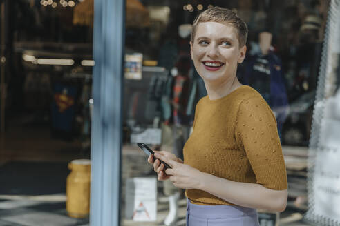 Happy woman holding smart phone looking away while standing in city - MFF06776