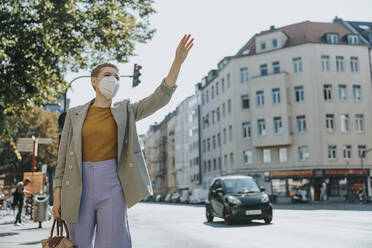 Woman wearing protective face mask calling taxi by waving standing on street in city - MFF06779
