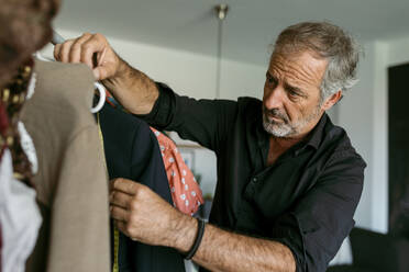 Mature male tailor measuring clothes on coathanger at work studio - VABF03709