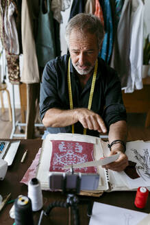 Talented tailor giving information about fabric while vlogging in studio - VABF03730