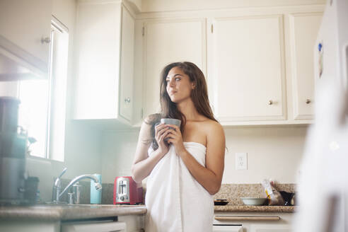 Thoughtful woman wearing towel holding coffee cup while standing in kitchen at home - AJOF00426