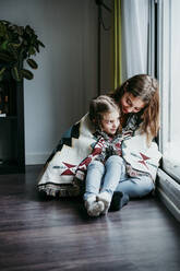 Girl sitting on sitter lap while sitting by window at home - EBBF01109