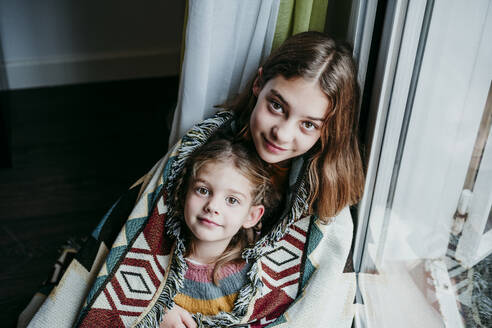 Sisters covered in blanket sitting by window at home - EBBF01112