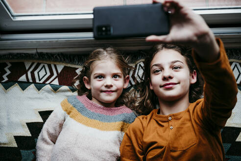 Sisters taking selfie through mobile phone while lying on blanket at home - EBBF01121