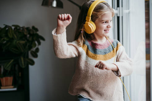 Girl wearing headphones dancing while standing by window at home - EBBF01130