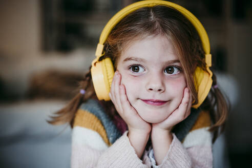 Cute girl with headphones and head in hands looking away while standing at home - EBBF01136