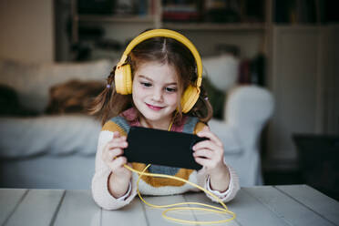 Smiling girl wearing headphones using mobile phone while standing at home - EBBF01139
