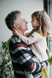 Father looking at daughter while carrying in arms at home - EBBF01142