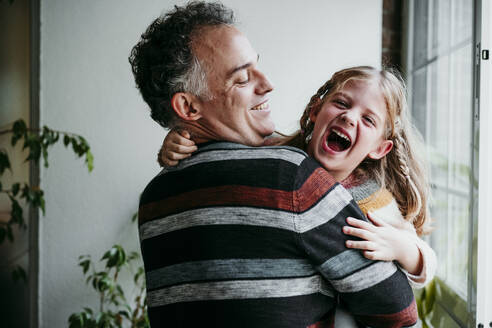 Smiling father carrying playful daughter while standing by window at home - EBBF01145