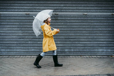 Girl wearing raincoat and jump boot holding umbrella while walking on sidewalk - EBBF01154