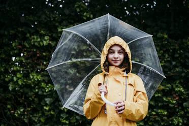 Girl wearing raincoat holding umbrella while standing against leaf wall - EBBF01157