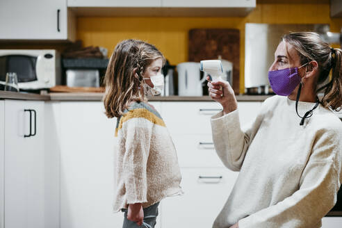 Mother wearing face mask checking temperature of daughter while sitting at home - EBBF01181