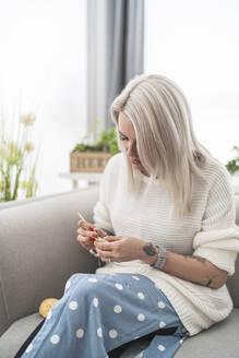 Woman making pacifier using wool while sitting on sofa at home - SNF00689