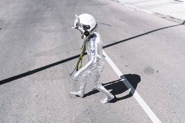 Boy in astronaut costume walking on road in city - JCMF01585