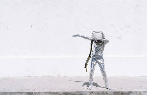 Boy in astronaut costume dabbing movement while standing against wall - JCMF01591
