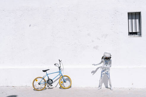 Boy in astronaut costume standing by bicycle on sidewalk in city - JCMF01594