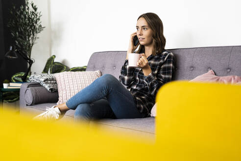 Young woman with coffee cup talking on mobile phone while sitting on sofa at home - GIOF09335