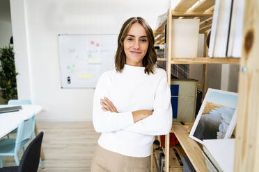 Smiling confident businesswoman standing with arms crossed at office - GIOF09395
