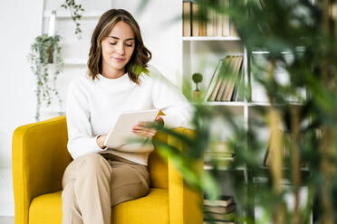 Businesswoman using digital tablet while sitting on sofa at office - GIOF09398