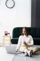 Businesswoman with coffee cup using laptop while sitting on floor at office - GIOF09401