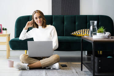 Smiling businesswoman using laptop while sitting on floor at office - GIOF09404