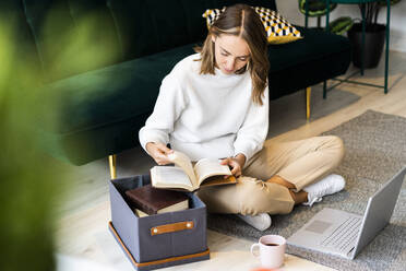 Businesswoman reading book while sitting by laptop and box on floor at office - GIOF09407