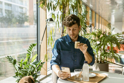 Handsome businessman using mobile phone while drinking coffee at table in cafe - VABF03738