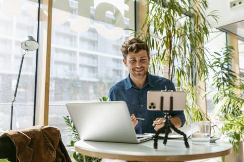 Smiling businessman having video conference on smart phone at cafe - VABF03753
