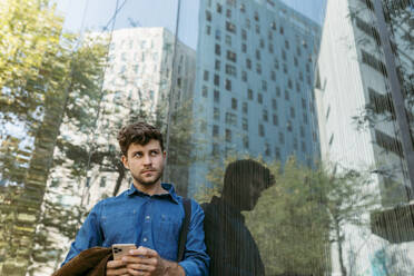 Thoughtful young businessman leaning on glass wall of modern office building - VABF03768
