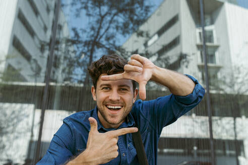 Cheerful businessman making finger frame against modern glass building - VABF03771