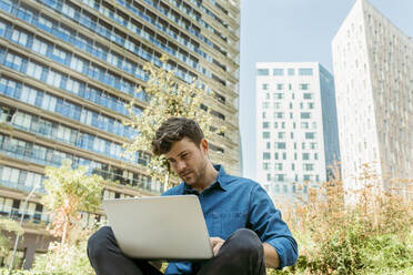 Handsome businessman using laptop while sitting against modern buildings - VABF03780