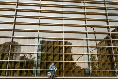 Young businessman standing by modern office building - VABF03789