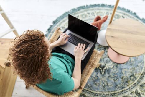 Curly redhead man using laptop at studio apartment - FMKF06636