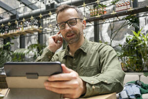 Businessman adjusting in-ear headphones while using digital tablet at cafe - VPIF03215