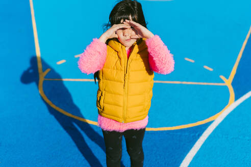 Girl shielding eyes while standing at basketball court on sunny day - ERRF04658
