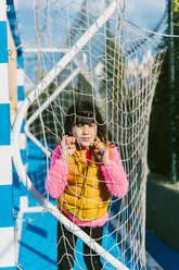 Cute girl leaning on goal post net at soccer court during sunny day - ERRF04661