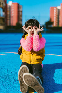 Girl forming binoculars with fingers while sitting on sports court during sunny day - ERRF04664